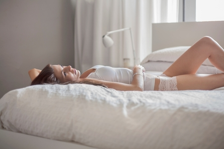 Young woman relaxing in bed LANG_EVOIMAGES