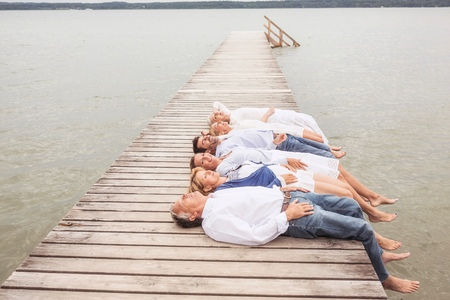 50 54 years: Group of friends lying in a row, on pier LANG_EVOIMAGES