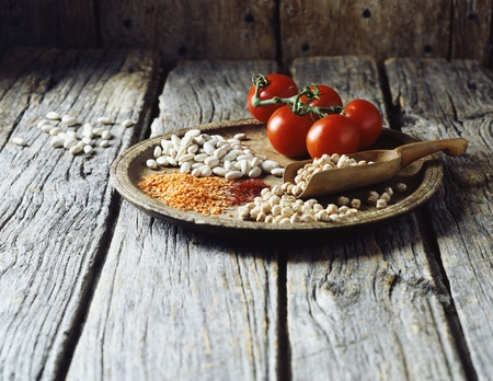 High angle view of red lentils, butter beans, split peas, saffron and vine tomatoes on wooden plate