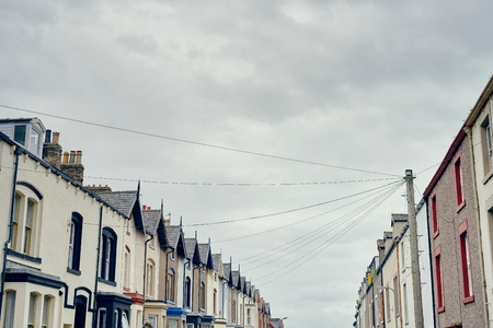 cumbria: Low angle view of terraced houses with telegraph pole and wires, Maryport, Cumbria, UK