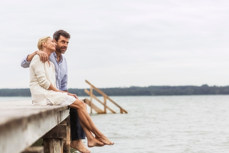 50 54 years: Mature couple sitting on edge of pier, relaxing LANG_EVOIMAGES