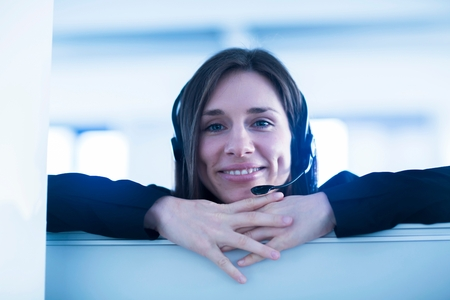 screen partition: Young woman wearing telephone headset looking over partition screen at camera smiling