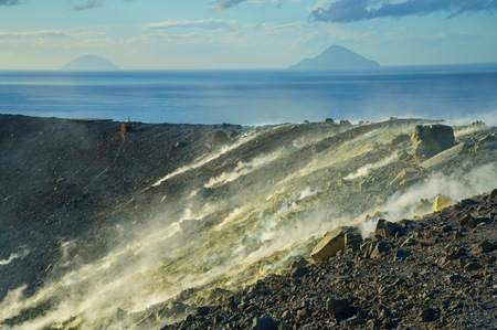 Sulphur and fumaroles smoke on Gran Cratere; The Islands of Alicudi and Filicudi in the background, Vulcano Island, Aeolian Islands, Sicily, Italy