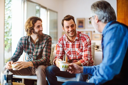 50 54 years: Mature man and two adult sons drinking coffee in living room