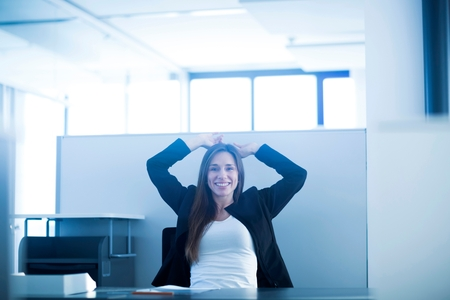 screen partition: Young woman sitting at desk in office hands behind head looking at camera smiling LANG_EVOIMAGES