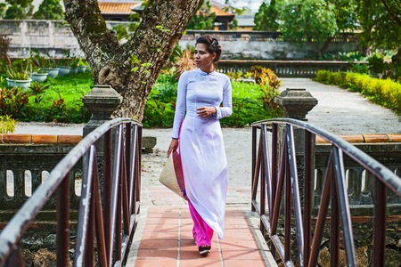 Mid adult woman wearing ao dai dress holding conical hat walking on footbridge looking away, Hue, Vietnam