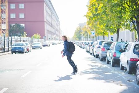 Young male urban skateboarder swerve skateboarding on road LANG_EVOIMAGES