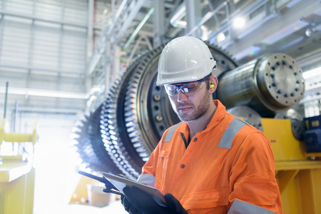 boiler suit: Worker with digital tablet in front of gas turbine in gas-fired power station