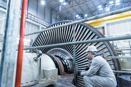 boiler suit: Engineer inspecting steam turbine in gas-fired power station LANG_EVOIMAGES
