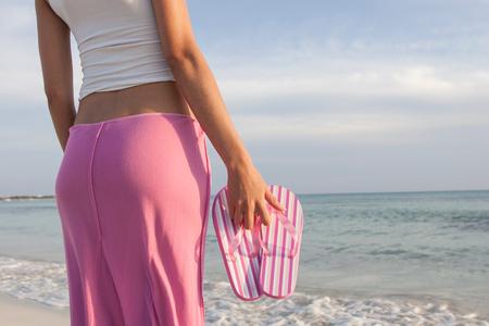 flip flops: Cropped shot of woman on beach holding striped pink flip flops, Majorca, Spain