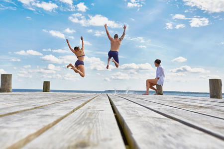 Young woman sitting on post on wooden pier, watching friends as they jump into sea
