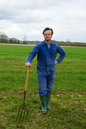 Portrait of farmer leaning on pitch fork in field