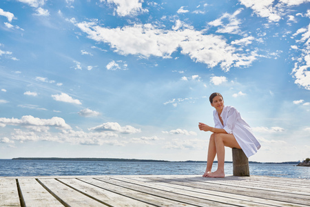 Young woman sitting on post on wooden pier, looking away