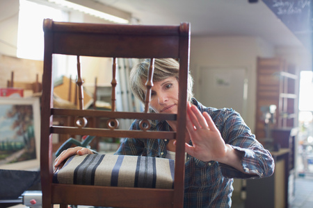 Woman in workshop examining chair