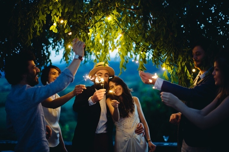 Group of friend holding lit sparklers, outdoors, evening LANG_EVOIMAGES