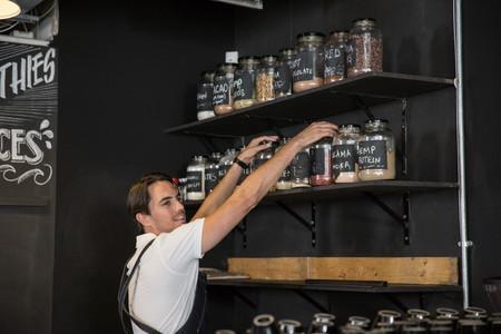 Restaurateur arranging jars on shelf LANG_EVOIMAGES