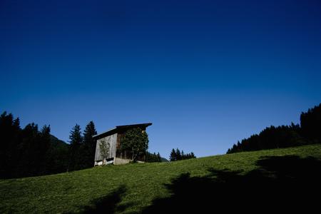 abodes: Shack on hillside against blue sky