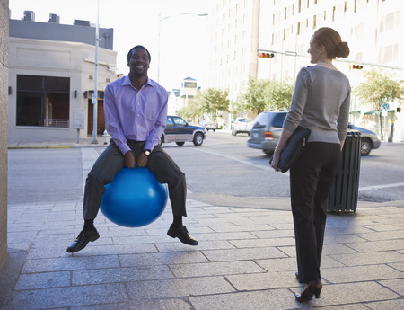 out of context: Businessman on blue ball in street