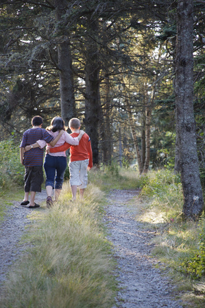 brotherly love: Mom walking with sons in woods