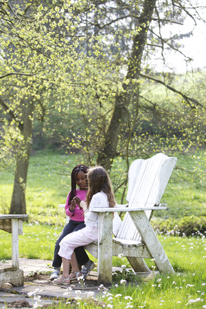 trusted: girls talking in a chair on a garden LANG_EVOIMAGES