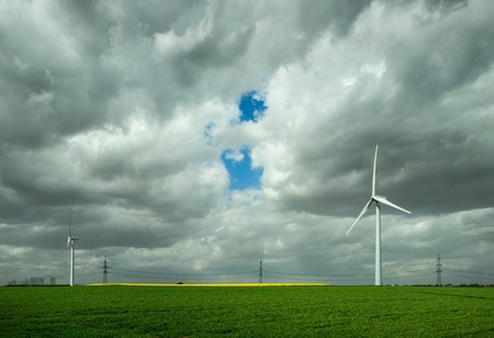 Wind turbines and distant view of browncoal fired power station on horizon, Allrath, Nordrhein-Westfalen, Germany LANG_EVOIMAGES