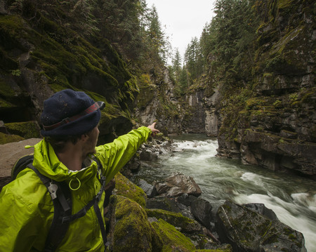 Hiker with headlamp points towards the 300 foot granite cliffs that encompass Coquihalla Canyon provincial Park and the Othello Tunnels. Part of the Trans-Canada Trail, Hope, British Columbia, Canada