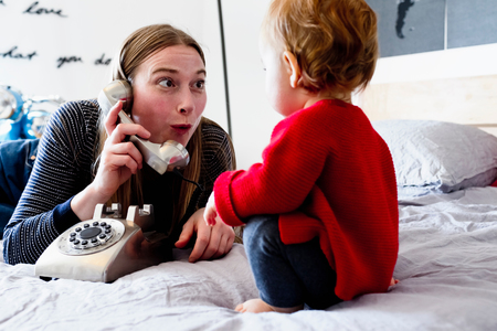 Baby girl and mother on bed pulling face at landline telephone