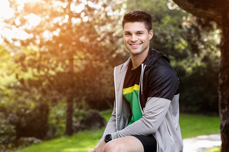 Portrait of young athlete in park LANG_EVOIMAGES