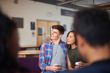common room: Young student couple with takeaway coffee in common room
