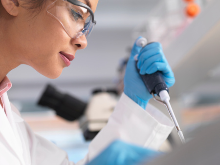 Vědec pipetoval vzorek do lahvičky během experimentu v laboratoři LANG_EVOIMAGES
