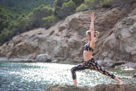 Young woman practicing yoga warrior position on sea rocks, Majorca, Spain
