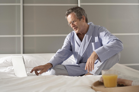 Puzzled senior man on bed typing on laptop