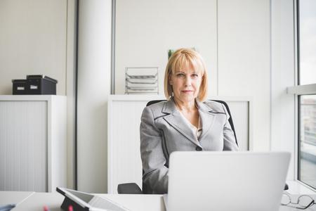 Portret dojrzały bizneswoman przy biurowym biurkiem