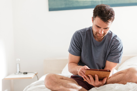 Man sitting on bed using digital tablet LANG_EVOIMAGES