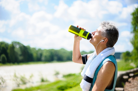 Senior male runner drinking from water bottle by river LANG_EVOIMAGES