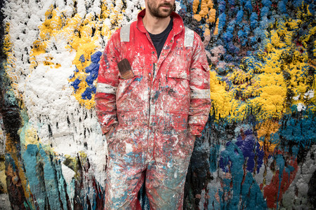 Mid section of male ship painter in front of paint splattered wall in ship painters yard