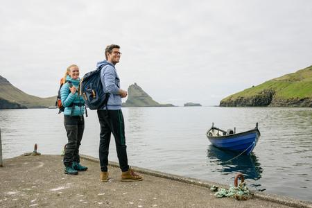 Hikers on pier, Vagar, Faroe Islands LANG_EVOIMAGES