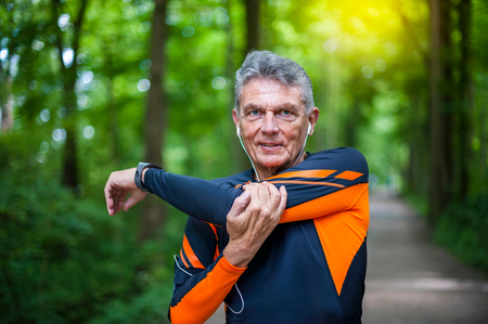 65 69 years: Senior male runner stretching arms in forest park