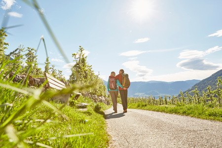 54: Mature couple hiking along country road, rear view, Meran, South Tyrol, Italy