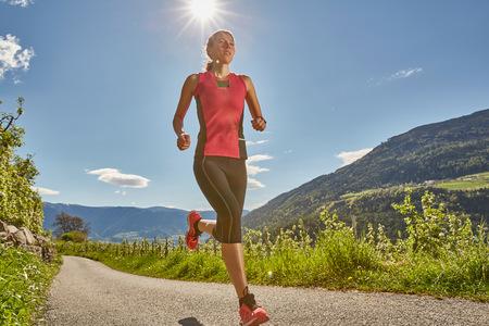 Young woman running along rural road, Meran, South Tyrol, Italy