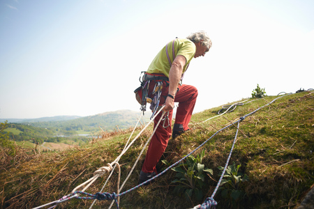 cumbria: Rock climber on hillside preparing climbing rope