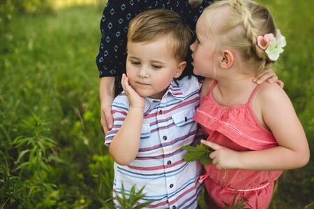 Girl whispering in brothers ear in meadow