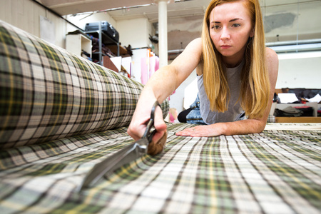 Young woman cutting fabric in leather jacket manufacturers