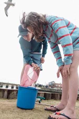 angled: Boy and girl emptying fishing net into bucket
