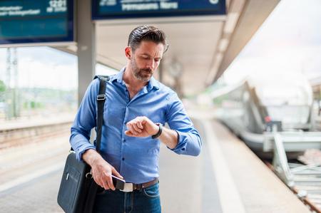 Mature businessman checking wrist watch on railway platform