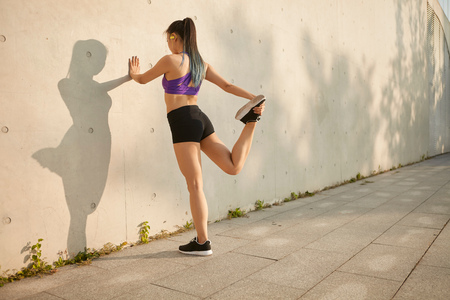 spandex: Woman leaning against wall stretching leg