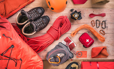 Overhead view of climbing equipment with climbing helmet, first aid kit, climbing boots and climbing ropes LANG_EVOIMAGES