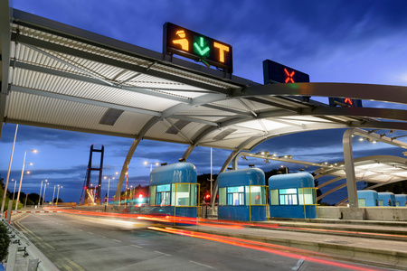Night view of cars passing through toll booth at bridge LANG_EVOIMAGES