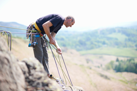 cumbria: Rock climber holding climbing ropes looking down