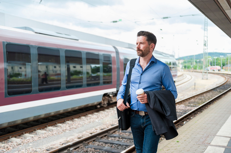 one mature man only: Mature businessman with takeaway coffee walking along on railway platform